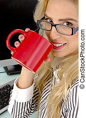 side pose of businesswoman holding mug and looking at camera...