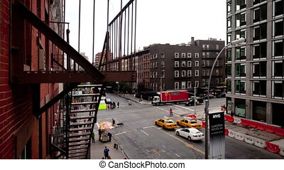 timelapse of a manhattan street, shot from the high line park with a fire escape in the foreground