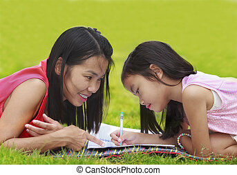 Mon and baby take a home work on the green nature