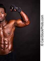 Muscular man flexing his biceps - African model flexing his...