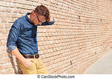 casual man standing upset by brick wall - casual young man...