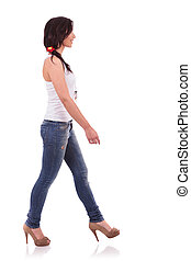 casual woman walking to side - side view of a casual young...