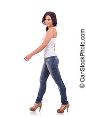casual woman walking - full length of a casual young woman...