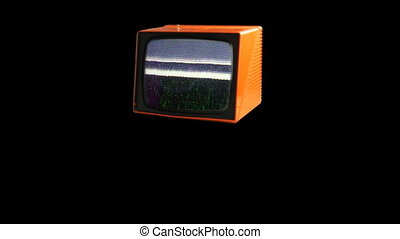 Stop motion of a fantastic retro orange television spinning around with static on screen