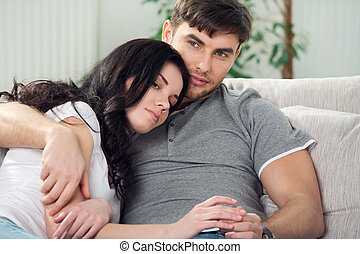 young couple are sitting down on a couch