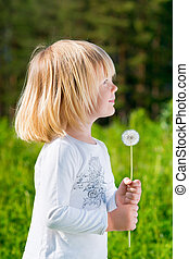 Cute smiling little boy with a dandelion in his hands