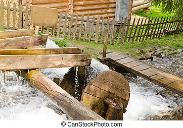 Small wooden waterwheel - Flowing river water rushing from a...