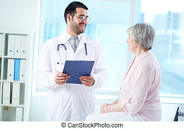 Interacting with patient - Confident doctor with stethoscope...