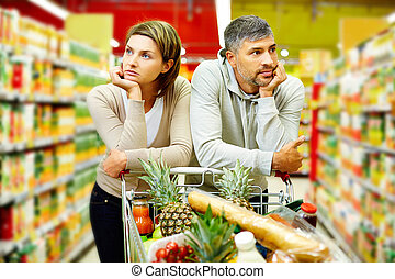 Couple in supermarket - Image of young couple with cart in...
