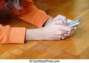 Sending a message - Teen girl lying on wooden parquet floor...