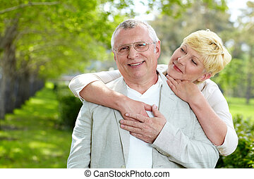 Man and woman - Portrait of happy mature woman hugging her...