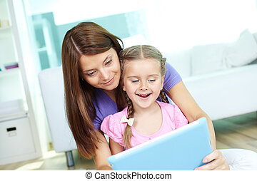 New technology - Mother and daughter using touchpad together...