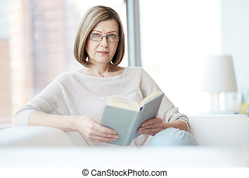 Reading book - Portrait of mature woman with book looking at...
