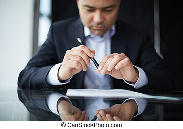 Reading contract - Close-up of male hands with pen over...