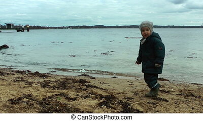 Child throwing sea shells in water, polluted beach