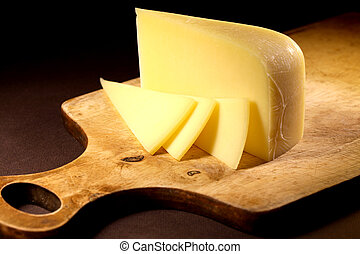 Cheese On Wood - Sliced cheese on wooden cutting board on...