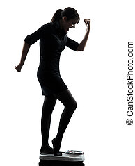 woman standing on weight scale  happy silhouette