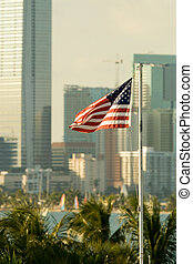 American Flag - American flag fluttering with city in the...