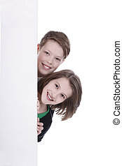 Girl and boy behind an empty wall isolated on white