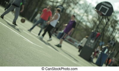 Teenagers playing basketball in a city park. Blured with...