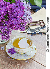summer cup of tea with lilac flowers and vintage photos