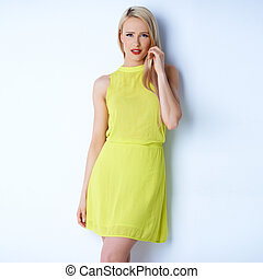 Attractive blond young woman posing in yellow dress against...