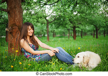 Woman play with her dog - golden retriever in the park