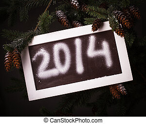 Chalkboard on the pine brach under the snow with 2014 new...