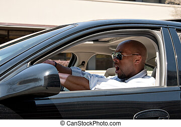Driving Has Road Rage - An irritated business man driving a...