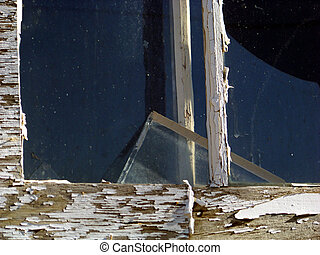 A shard of glass rests in a weathered window frame.