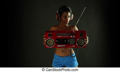 sexy young woman dances and poses holding a retro red ghettoblaster