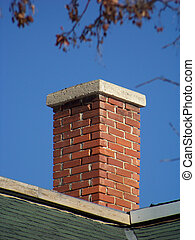 An aging red brick chimney on a clear day.