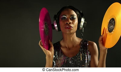 sexy young woman dancing around holding 2 coloured record...