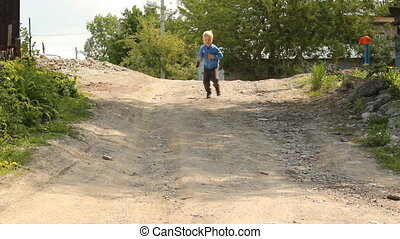 Blonde boy running on rural road