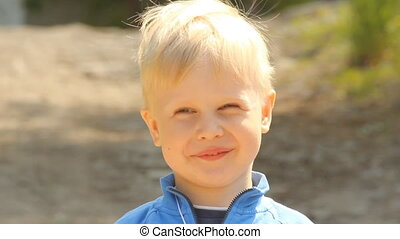 Positive blond boy smiling outdoors