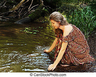 Beautiful girl in floral dress looks at his reflection in...