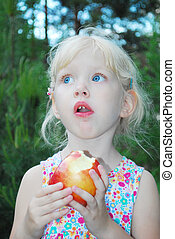 little girl are eating apples - In the summer, bright sunny...