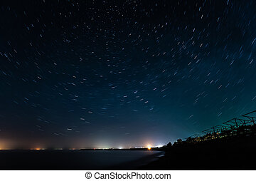 Night coast under star trails rounded