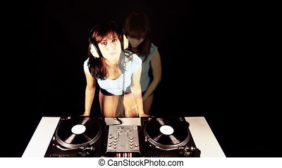 beautiful young female dj, behind the decks at a club