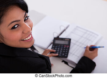 Businesswoman Doing Calculations - Portrait Of Young...