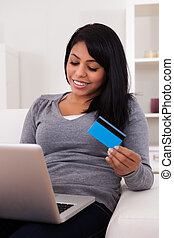 Young Woman Shopping Online - Happy Young Woman Sitting On...