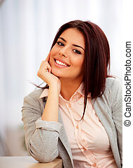 Young confident smiling woman sitting at the table