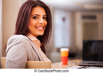 Young businesswoman sitting at desk and working. Smiling and...