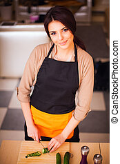 Beautiful young smiling woman cooking healthy salad at home