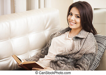 Happy young woman reading a book at home