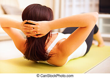 Athletic young woman working out at home lying on a mat...