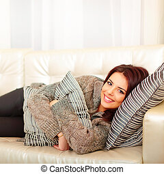 Happy young beautiful woman relaxing on sofa at home and...