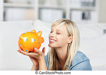 Smiling woman looking at her piggy bank - Smiling woman...