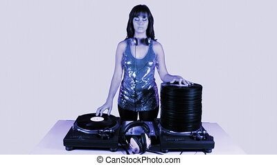 beautiful young female dj, behind the decks with piles of...
