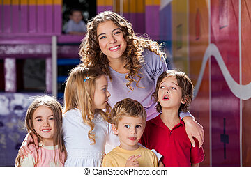 Happy Teacher With Cute Children In Preschool - Portrait of...